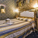 hotel noemi camera oro blu e bianco vista letto con bicchieri e champagne