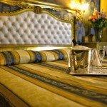hotel noemi camera oro e blu vista letto da vicino con bicchieri e champagne
